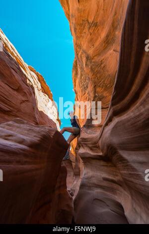 Randonneur fille escalade partie étroite de Peekaboo Gulch Canyon Banque D'Images
