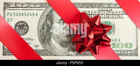 Un cadeau. Une centaine de loi avec arc rouge et ruban Banque D'Images