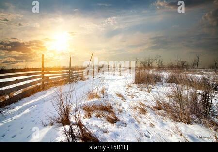 Clôture en bois en hiver, au coucher du soleil sur le terrain Banque D'Images
