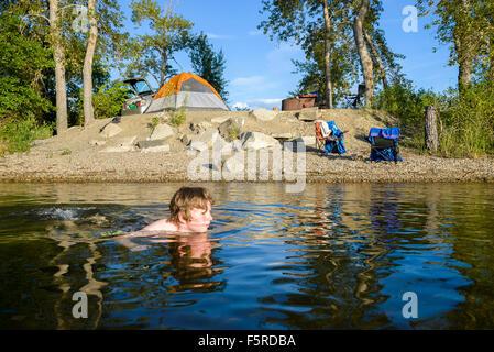 Garçon nage dans l'eau à bord du lac camping,sẁiẁs Provincial Park, Osoyoos, Colombie-Britannique, Canada Banque D'Images