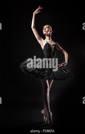 Ballerine Slim dans un corset noir et noir tutu. Répétition générale au théâtre. Ballet classique. Banque D'Images