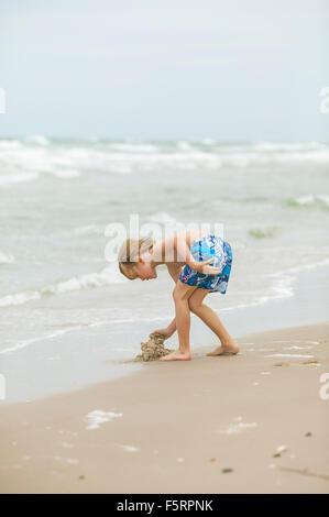 Le Danemark, dans le Jutland, Vendsyssel, Lokken, Boy (8-9) building sandcastle Banque D'Images