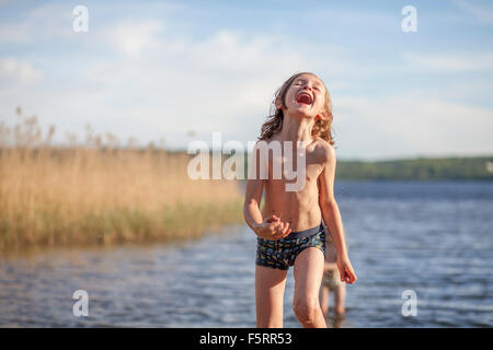 La Suède, Vastergotland, Lerum, lac Aspen, Boy (8-9) standing in lake Banque D'Images