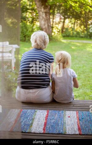 La Suède, Narke, Filipshyttan, Woman sitting with girl (6-7) on porch Banque D'Images