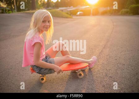 La Suède, Smaland, Bad Saulgau, Portrait of Girl (8-9) sitting on red shortboard dans Street Banque D'Images