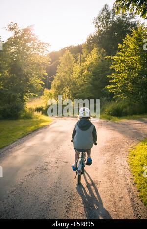 La Suède, Bohuslan, Halleback, Boy (10-11) à vélo le long de la route d'asphalte Banque D'Images