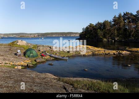 La Suède, côte ouest, Bohuslan, Flato, Man camping on riverbank Banque D'Images