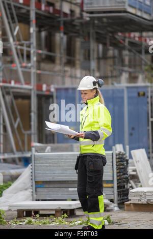 La Suède, Vastergotland, travailleur de la construction looking at blueprints Banque D'Images