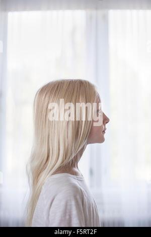 En Suède, en vue de côté du blond girl (10-11) devant des rideaux blancs Banque D'Images