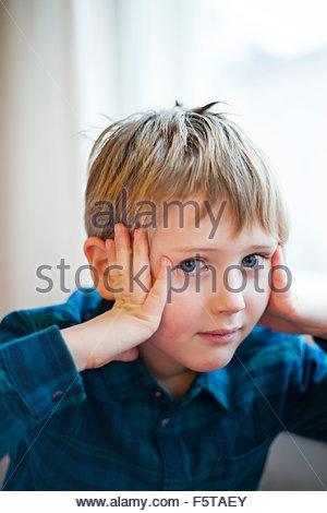 La Finlande, Boy (6-7) holding head in hands Banque D'Images