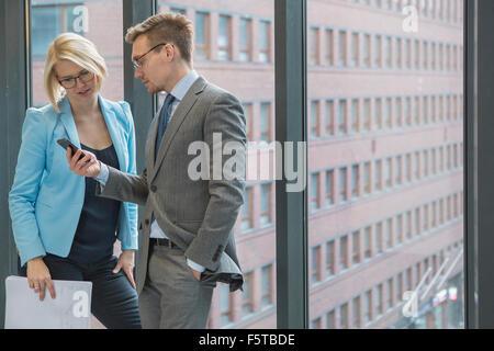 La Finlande, Helsinki, des gens d'affaires à la recherche sur téléphone mobile par fenêtre Banque D'Images