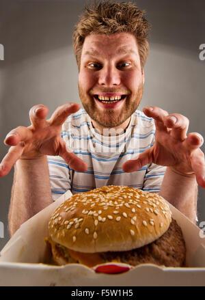 Portrait d'homme heureux prépare à manger burger Banque D'Images