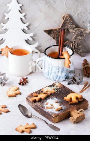 Shortbread cookies de Noël pour les tasses, deux tasses de thé chaud et le sucre en poudre sur table avec nappe blanche avec déco de Noël