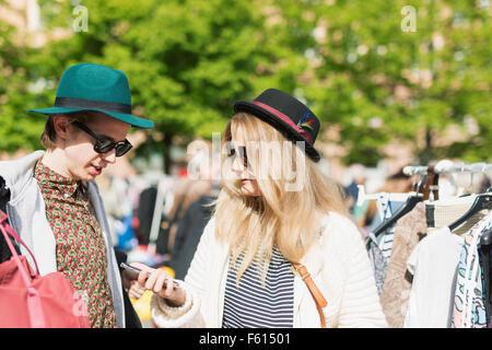 Jeune femme montrant téléphone mobile à un ami tout en se tenant au marché aux puces Banque D'Images