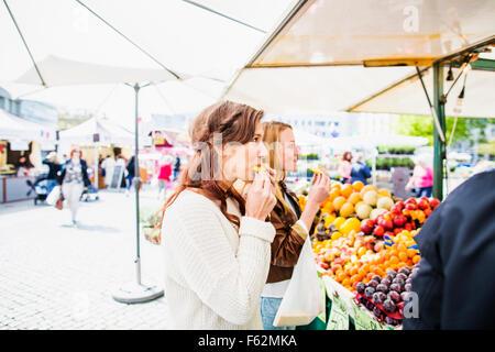 Les femmes mangent des fruits en faisant vos achats chez market Banque D'Images