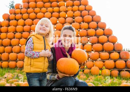 Une belle femme souriante et cute little girl holding pumpkins en face de gros tas de citrouilles orange à l'automne Banque D'Images