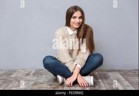 Beautiful smiling girl with long hair en beige pull et jeans assis sur un plancher en bois avec les jambes croisées Banque D'Images