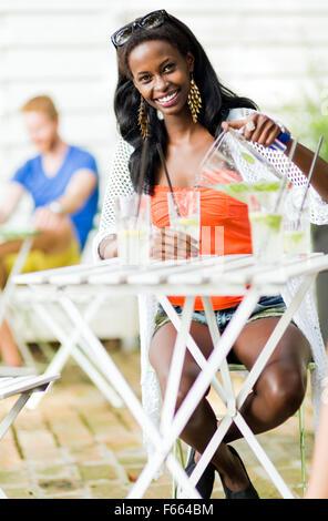 Belle femme noire assis à une table de café en plein air et de boire une boisson rafraîchissante pendant une chaude journée d'été