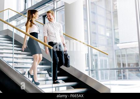 Des collègues de parler dans les escaliers et le flirt Banque D'Images