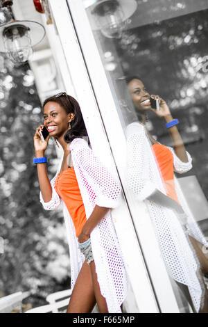 Belle black woman talking on phone and smiling durant une journée d'été et son reflet montrant sur la fenêtre Banque D'Images