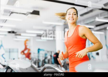 Belle jeune femme s'exécutant sur un tapis roulant dans une salle de sport et smiling Banque D'Images