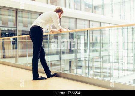 Businessman holding phone sur balcon et d'avoir une pause