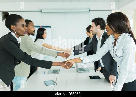 Les gens d'affaires se serrer la main avant de s'asseoir à une table de conférence. Banque D'Images