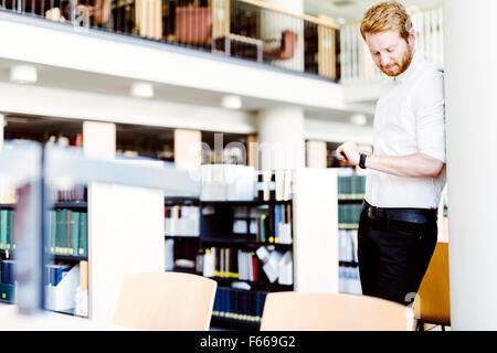 Handsome student consultation en bibliothèque et smiling Banque D'Images