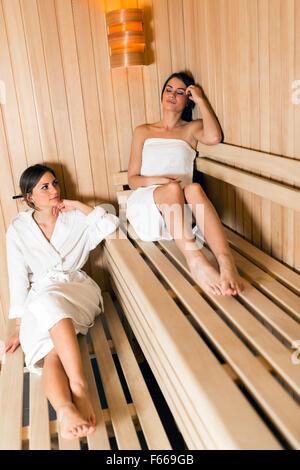 Deux belles femmes en forme et vous détendre dans un sauna Banque D'Images