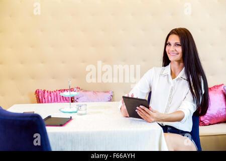 Belle jeune femme à l'aide de tablette dans un restaurant and smiling