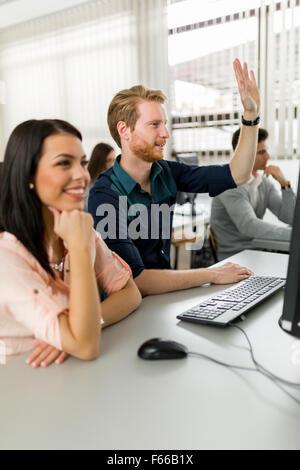 Belle jeune femme et un homme les mains dans la salle de classe tout en étant assis en face d'un ordinateur de bureau Banque D'Images