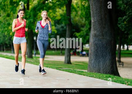 Deux femmes le jogging dans le parc et d'écouter de la musique