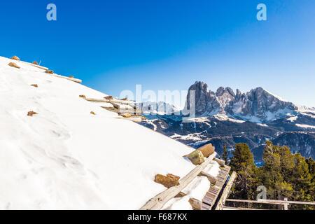 Toit recouvert de neige de log cabin en face de la Dolomite peaks couvert de neige et de conifère à Banque D'Images