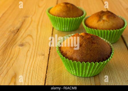 Muffins dans le livre vert porte-cupcake sur un fond de bois horizontal, selective focus Banque D'Images