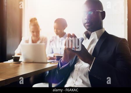 L'homme d'affaires noir grave assis en face de ses employés au bureau Banque D'Images
