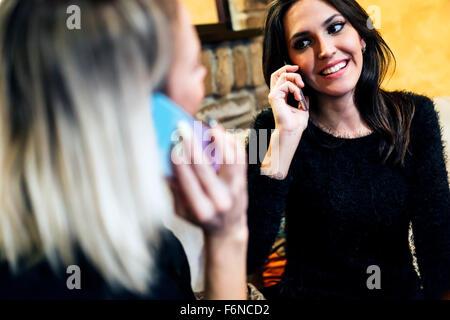 Deux belles femmes parlant au téléphone dans le café tout en étant heureux Banque D'Images