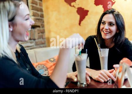 Deux femmes de boire et de parler dans le café tout en ayant un bon temps Banque D'Images