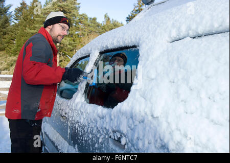 Un homme dans un woolly hat commence le long processus de compensation de la glace et de la neige à partir d'une Banque D'Images