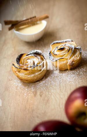 Pâtisserie au four en forme de rose avec du sucre en poudre sur le mouvement, la cannelle vanille fond apple Banque D'Images