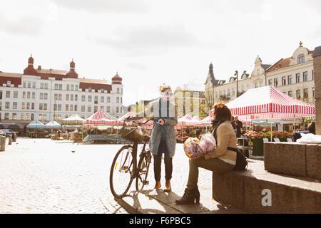 Les femmes mûres prenant pause après shopping in market Banque D'Images