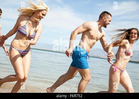 Groupe d'amis sur la plage s'amusant Banque D'Images