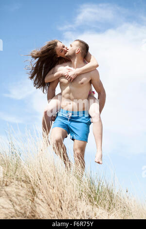 Man giving girlfriend piggyback ride on beach Banque D'Images