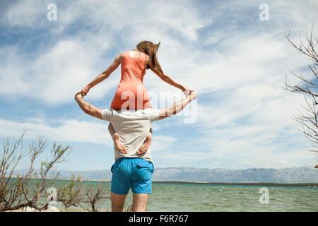 Jeune femme assise sur l'épaule de son petit ami Banque D'Images