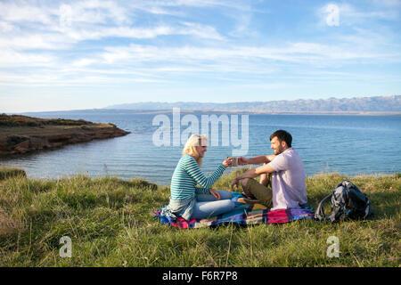 Jeune couple ayant un pique-nique sur le bord de l'eau Banque D'Images