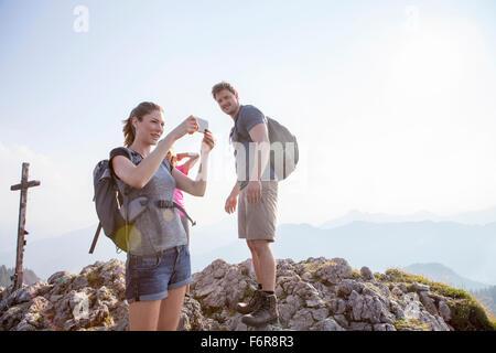 Groupe d'amis à prendre des photos de paysage de montagne Banque D'Images