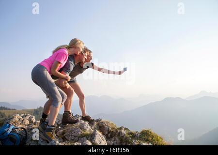 Groupe d'amis prendre photo sur sommet de montagne Banque D'Images