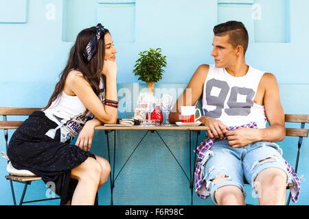 Young couple in restaurant en plein air de flirter Banque D'Images