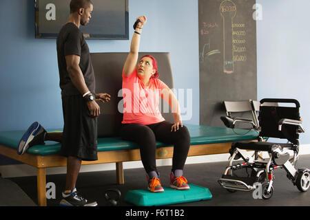 Femme handicapée de faire la thérapie physique avec formateur Banque D'Images