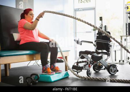 Femme handicapée de faire la thérapie physique en salle de sport Banque D'Images