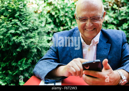 Hispanic businessman using cell phone Banque D'Images